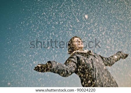 Young woman throwing snow on blue sky in background - joy and happiness emotions - stock photo
