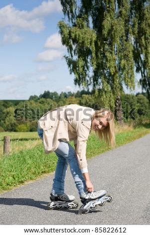 Young woman tightening inline skates on sunny asphalt road - stock photo