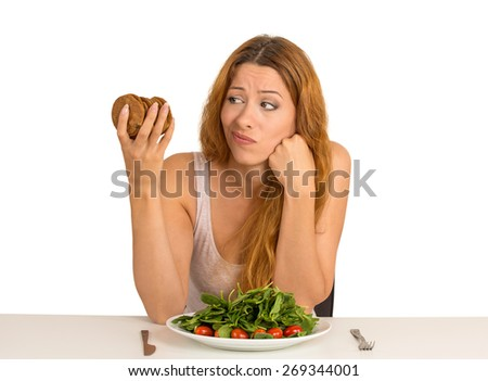 Young woman tired of diet restrictions deciding whether to eat healthy food or sweet cookies she is craving sitting at table isolated white background. Human face expression emotion. Nutrition concept - stock photo