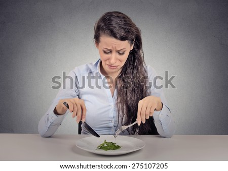 Young woman tired of diet restrictions eating green salad sitting at table isolated grey wall background. Human face expression emotion. Nutrition concept - stock photo