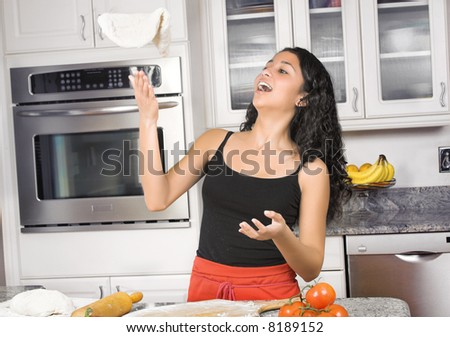 young woman tossing pizza dough in the air - stock photo
