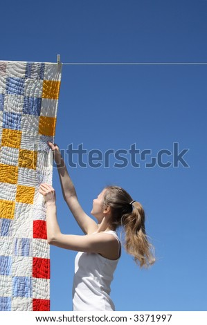 Young woman touching a bright patchwork counterpane hanging to dry on a clothes-line. - stock photo