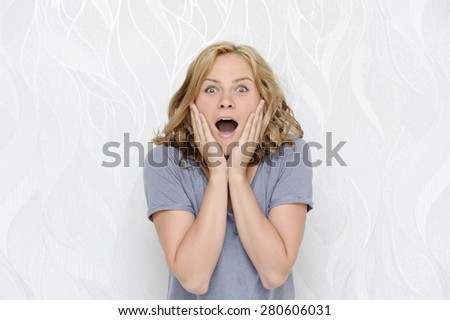 Young woman touching face in surprise - stock photo