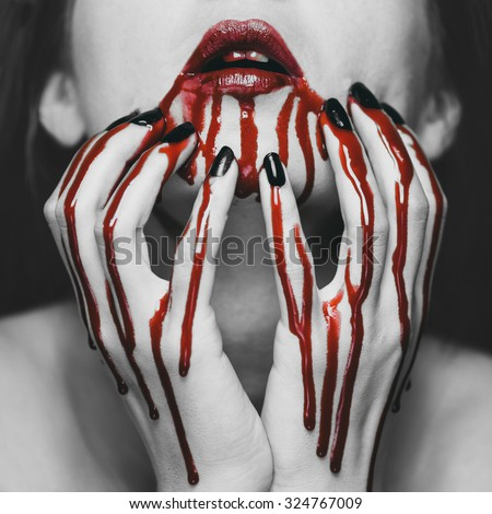 Young woman touching her face in blood. Halloween and horror theme. Black and white image with red elements