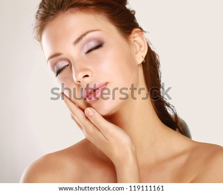 Young woman touching her face isolated on whire background - stock photo