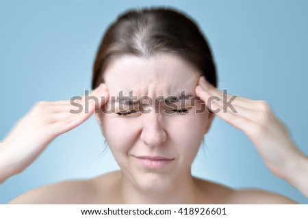 Young woman touching her head - stock photo