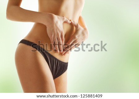 Young woman touching her stomach. Female with stomachache isolated on green background