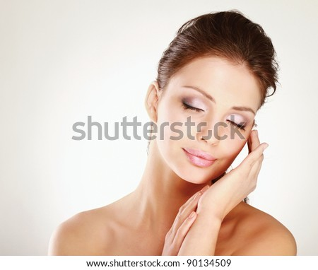 Young woman touching hr face isolated on whire background - stock photo