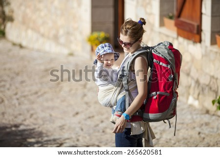 Young woman tourist carrying her little son in sling - stock photo