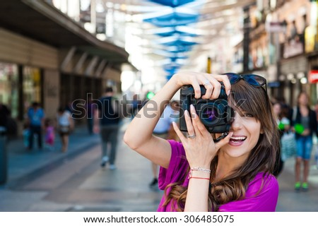 Young woman tourist holding a photo camera and taking picture in Plaza del Sol square, Madrid, Spain. - stock photo