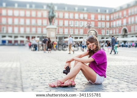 Young woman tourist holding a photo camera, sitting and looking at buildings in Plaza Mayor square, Madrid, Spain. Tourist attraction, statue of Felipe III in the background. - stock photo