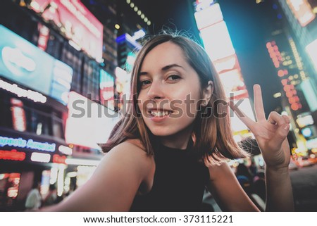 Young woman tourist laughing and taking selfie photo in New York City, Manhattan, Times Square. Female traveler and photographer takes selfie picture for her blog. - stock photo