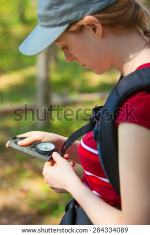 Young woman tourist looking on compass. Focus on compass. - stock photo