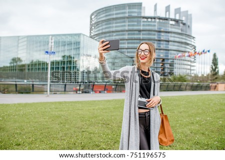 Young woman tourist making selfie photo with smartphone visiting European parliament in Strasbourg, France