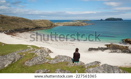 Young woman tourist sitting in front of a desert white beach with blue sea in the Isle of Lewis, Outer Hebrides, Scotland (UK) - stock photo
