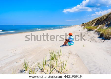 Young woman tourist sitting in sand on beautiful empty beach in Bialogora, Baltic Sea, Poland