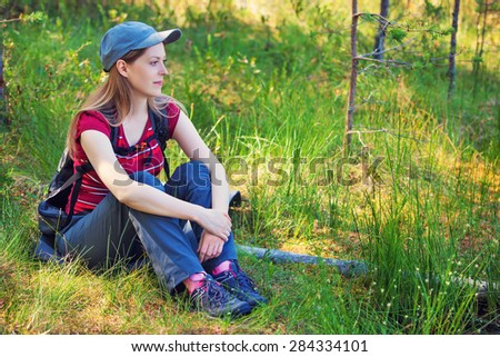 Young woman tourist sitting on grass in forest. - stock photo