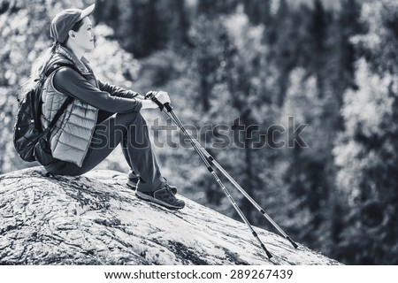 Young woman tourist sitting on mountain top and looking aside on forest. Black and white colors. - stock photo