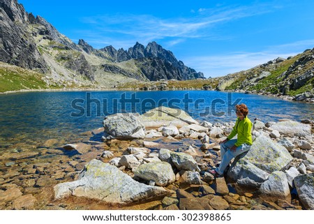 Young woman tourist sitting on rock on shore of lake in Starolesna valley, High Tatra Mountains, Slovakia
