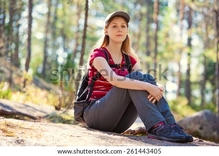 Young woman tourist sitting on stone in summer forest. - stock photo