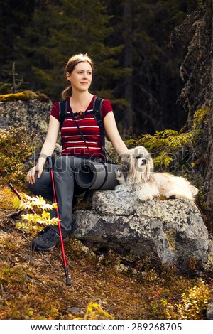 Young woman tourist sitting on stone with dog in autumn forest. - stock photo