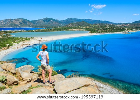 Young woman tourist standing on cliff looking at beautiful azure sea lagoon beach, Villasimius, Sardinia island, Italy