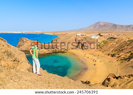 Young woman tourist standing on cliff looking at Papagayo beach, Lanzarote, Canary Islands, Spain
