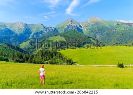 Young woman tourist standing on green meadow with yellow flowers and looking at summer landscape of Tatra Mountains, Slovakia