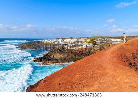 Young woman tourist standing on red lava rocks and looking at ocean waves, El Golfo, Lanzarote, Canary Islands, Spain