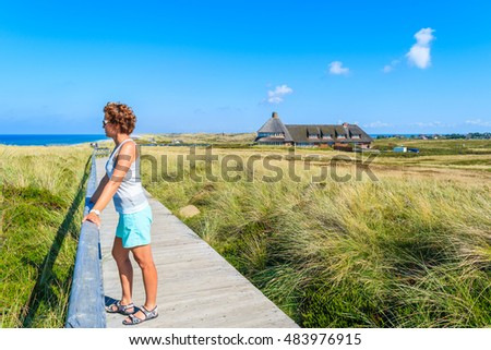 Young woman tourist standing on walking path along a coast of Sylt island, Germany