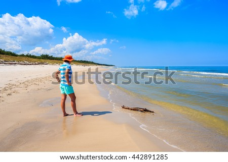 Young woman tourist standing on white sand beach in Bialogora, Baltic Sea, Poland
