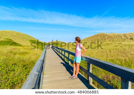 Young woman tourist standing on wooden walkway to beach among sand dunes on Sylt island, Germany