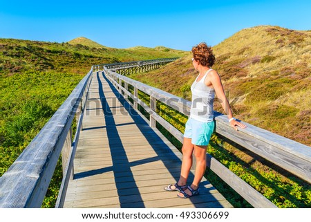 Young woman tourist standing on wooden walkway to beach in Wenningstedt, Sylt island, Germany