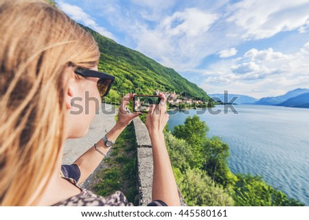Young woman tourist taking pictures with mobile phone on the coastline of Lake Como, Italy - stock photo