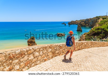 Young woman tourist walking along famous Praia Dona Ana beach with turquoise sea water and cliffs, Portugal