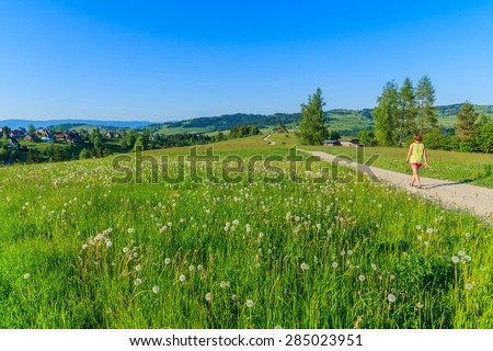 Young woman tourist walking on rural road along green meadow in Tatra Mountains, Poland