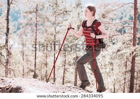 Young woman tourist walking on stones in forest. Bright white ir-style colors. - stock photo