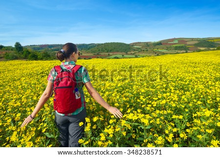 Young woman tourist walks on the background of colored fields.Traveling along Europe, freedom and active lifestyle concept - stock photo