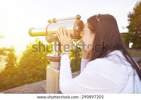 young woman tourist watching at the beautiful landscape from the telescope - stock photo