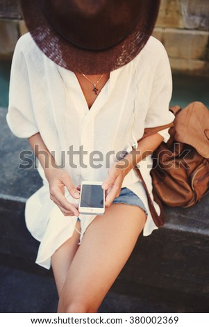 Young woman tourist with backpack using her mobile phone while sitting outdoors after walking in urban scene, stylish hipster girl chatting with friends on cell telephone during summer vacation - stock photo