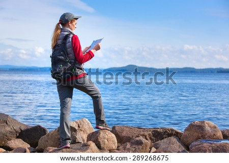 Young woman tourist with map and backpack standing on lake shore. - stock photo