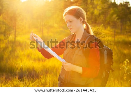 Young woman tourist with map portrait. Bright red sunset light. - stock photo