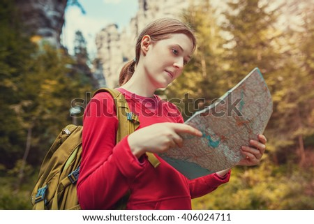 Young woman tourist with map portrait on forest background at autumn season. Focus on face. - stock photo