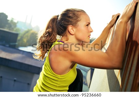 Young woman traceur climbing an obstacle while participating in parkour