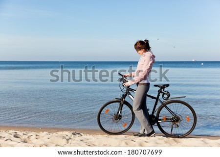 Young woman tracking her route on the smartphone gps during the bicycle trip on the beach. Sea in the background - stock photo
