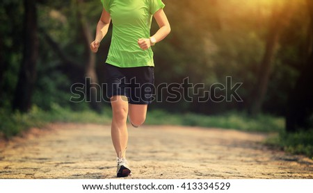 young woman trail runner running in forest