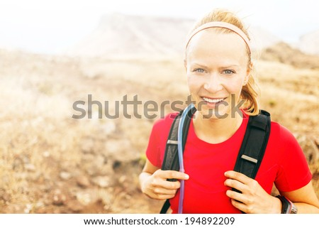 Young woman trail running in mountains on sunny summer day. Female runner exercising outdoors in nature, sunset. Cross country working out, sport and fitness concept. - stock photo