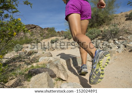 Young woman trail running outdoors at South Mountain Park in Phoenix, Arizona. - stock photo