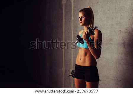 Young woman training biceps with dumbbells - stock photo