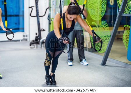 Young woman training exercise push ups with trx fitness straps in the gym  Concept sport workout healthy lifestyle. - stock photo